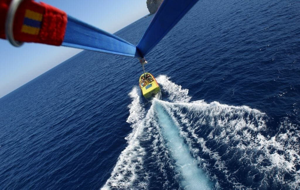 Straps of a parasail with cord to a yellow boat speeding on the ocean below
