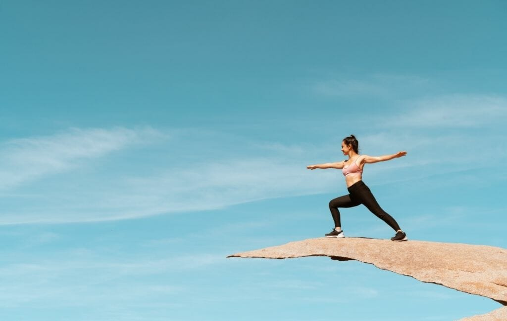 woman doing a warrior yoga pose on a thin rock called Potato chip Rock San Diego