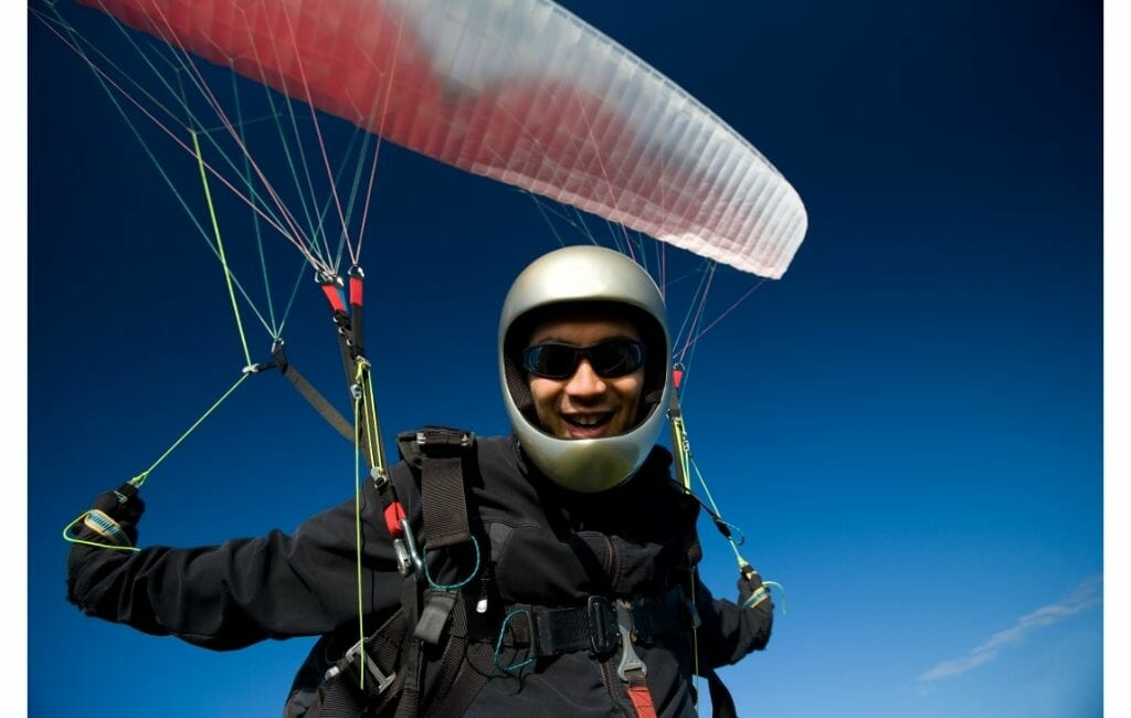 Paraglider with silver helmet and silver/red glider with deep blue sky in the background - San Diego Adventures