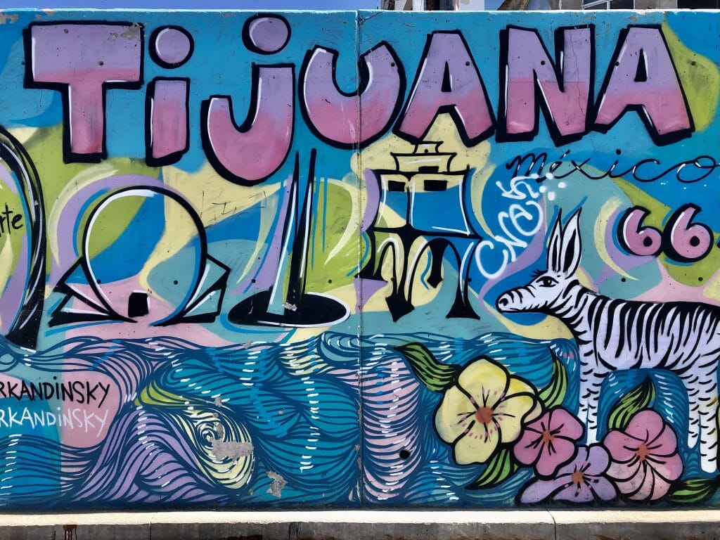 blue and purple wall mural with iconic things that Tijuana is known for, like the CECUT cultural center, the Tijuana zonkey etc