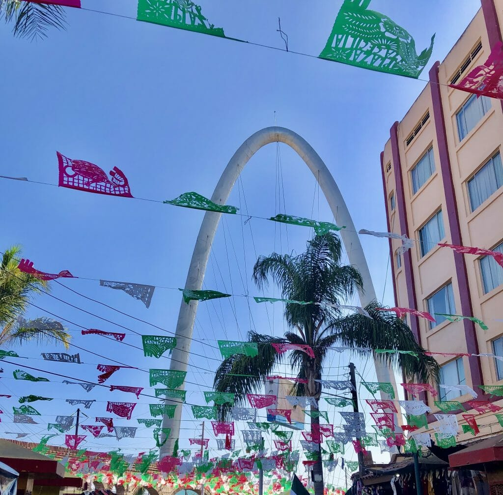Red white and green flags on strings above street with the tall Tijuana arch in the background
