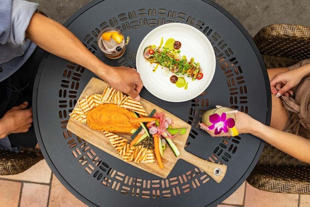 Flatlay of table with various plates and foods with a male and female hand reaching in