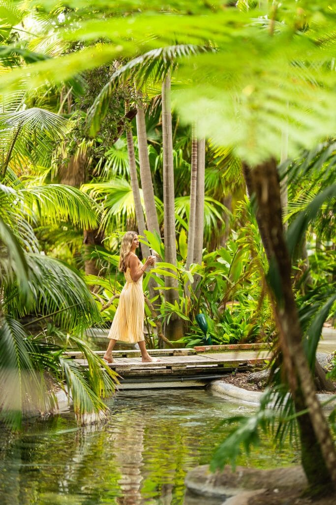 Woman in yellow dress walking on a wooden bridge over a small stream through a lush tropical forest at Bahia Resort Gardens