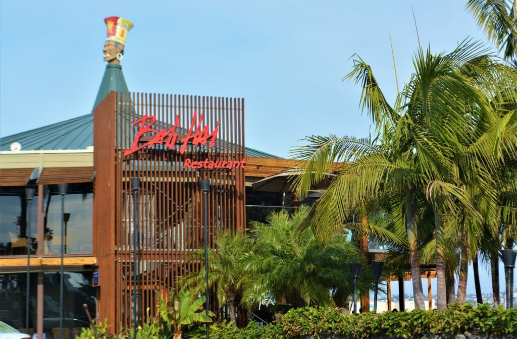 Bali Hai Restaurant San Diego - two story hut-inspired building with glass sides surrounded by palm trees - red sign on roof: Bali Hai