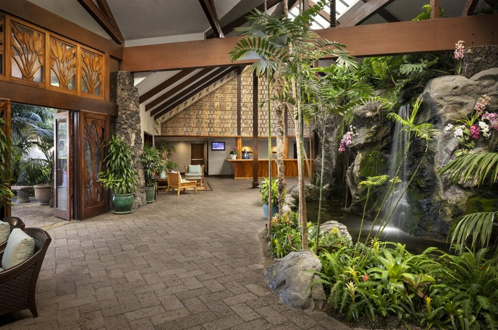 Catamaran Resort Lobby with lush plants and waterfall on the right and tropical/polynesian decor and architecture on the left