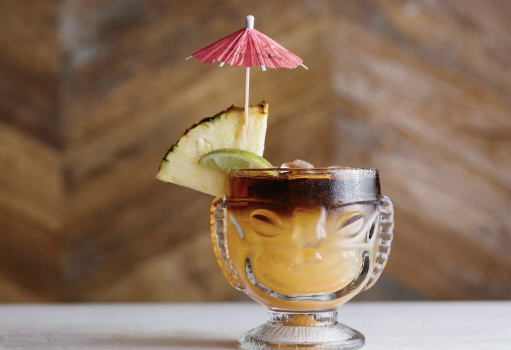 Mai Tai cocktail in a Tiki-inspired glass with slice of pineapple and pink umbrella