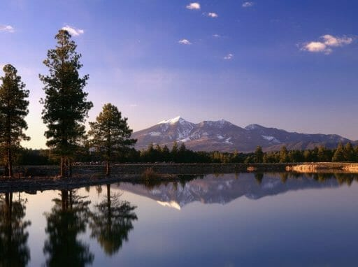 sunset photo of lake in the front, and snow-capped mountains in the back, reflecting in the lake