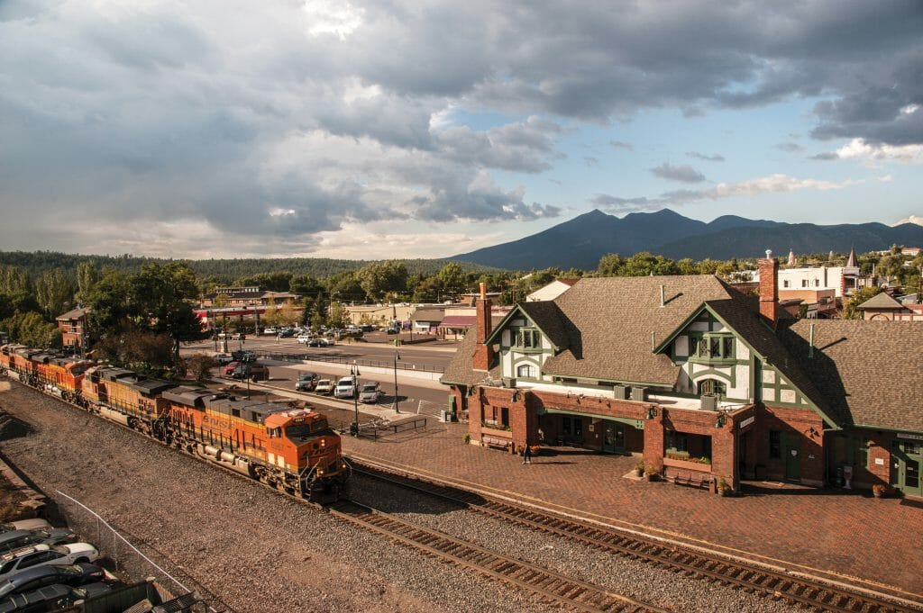 Aerial View of Flagstaff Train station / Flagstaff visitor center and a fright train passing by in front of it.