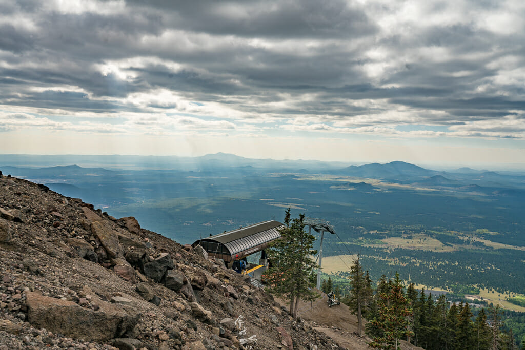steep gravel slope in the foreground, metal roof of the gondola station in the center and vast view of the valley and dramatic sky in the background