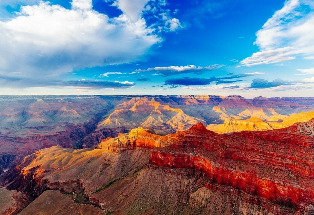 Blue sky and fluffy white clouds over the red rocks of the Grand canyon