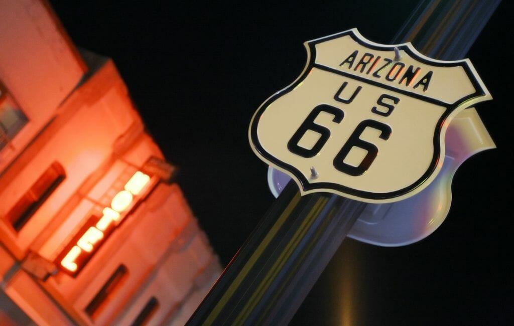 """Historic Route 66 Sign in the foreground, dark sky in the background behind it, a blurry building lid up by red neon sign reading """"hotel"""" on the left side of the image"""