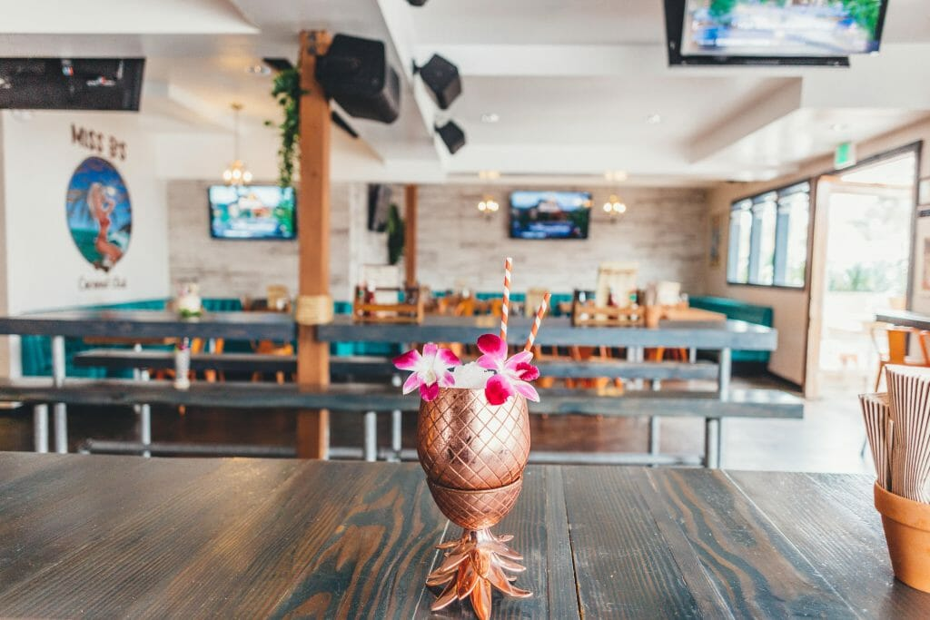 foreground: Wood table with pineapple-shaped copper cocktail glass decorated with pink flowers, background empty bar
