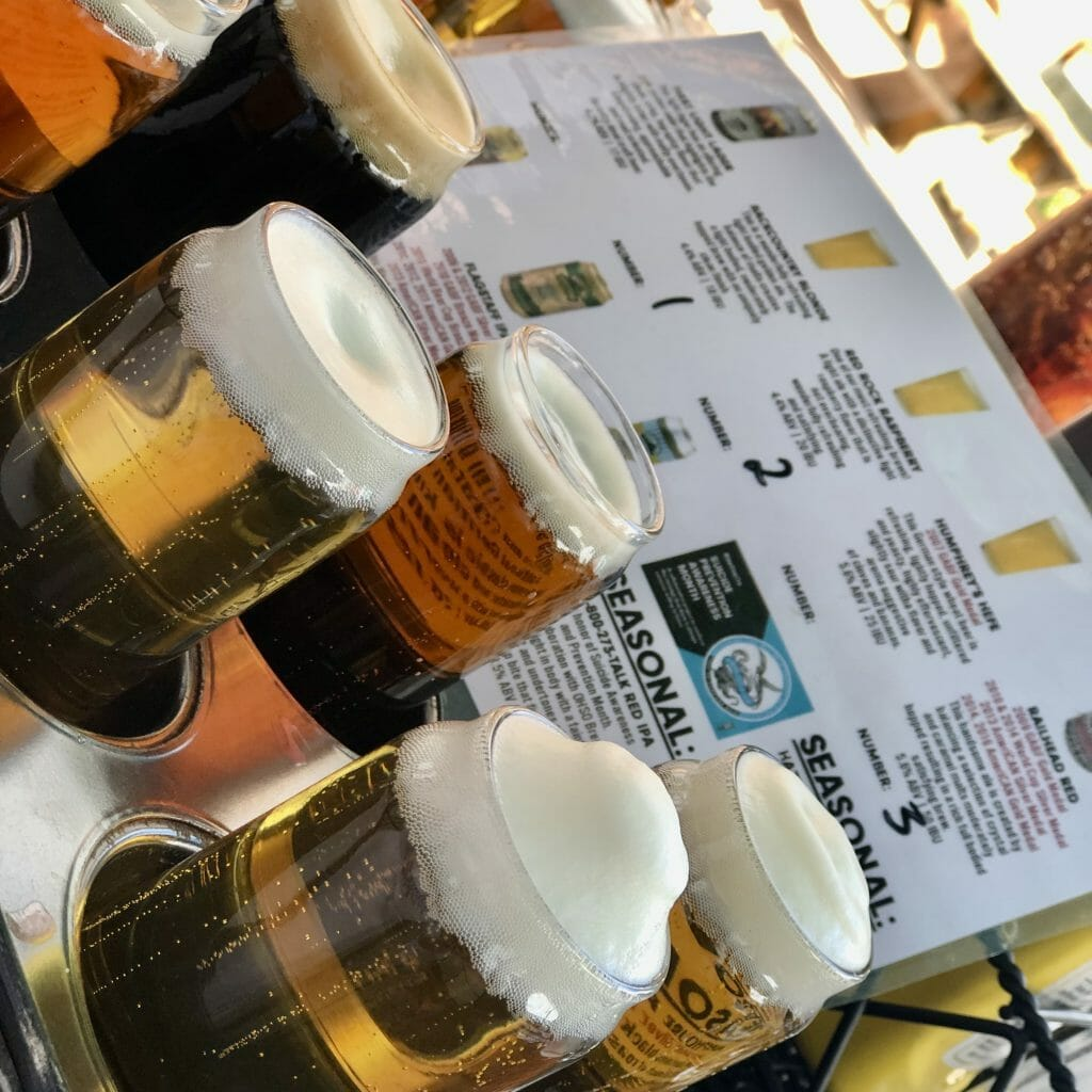Flight of beer samplers in a muffin tin with a beer menu in the background