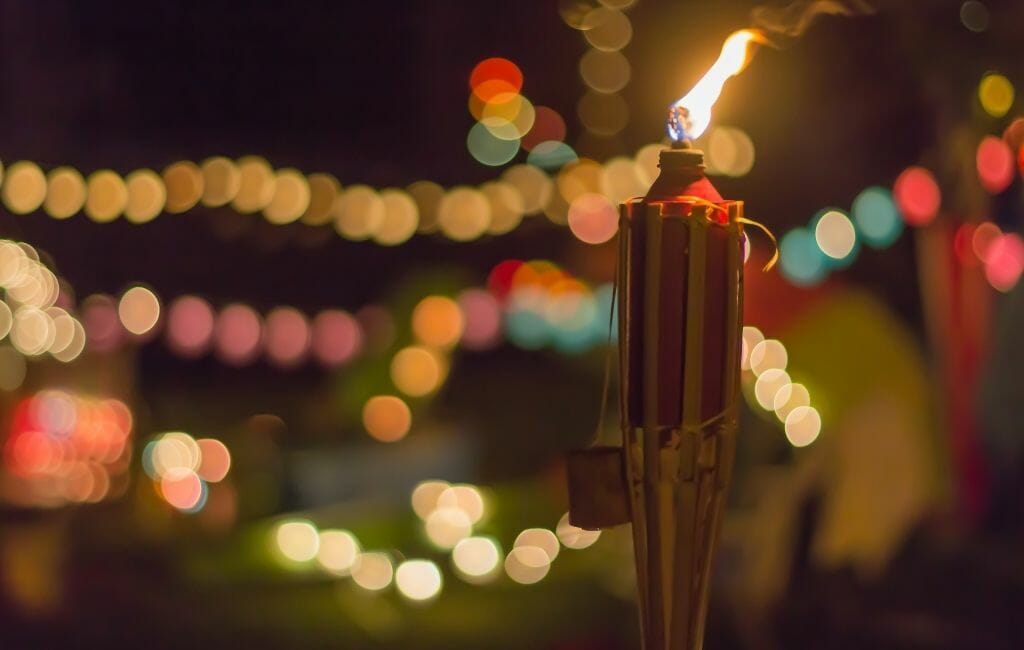 tiki torch in the foreground to the right, and colorful bokeh lights in the dark background