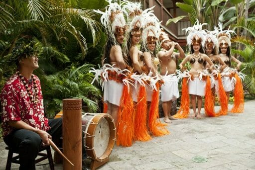 Performance of Polynesian dancers in orange palm skirts and white feather headdresses
